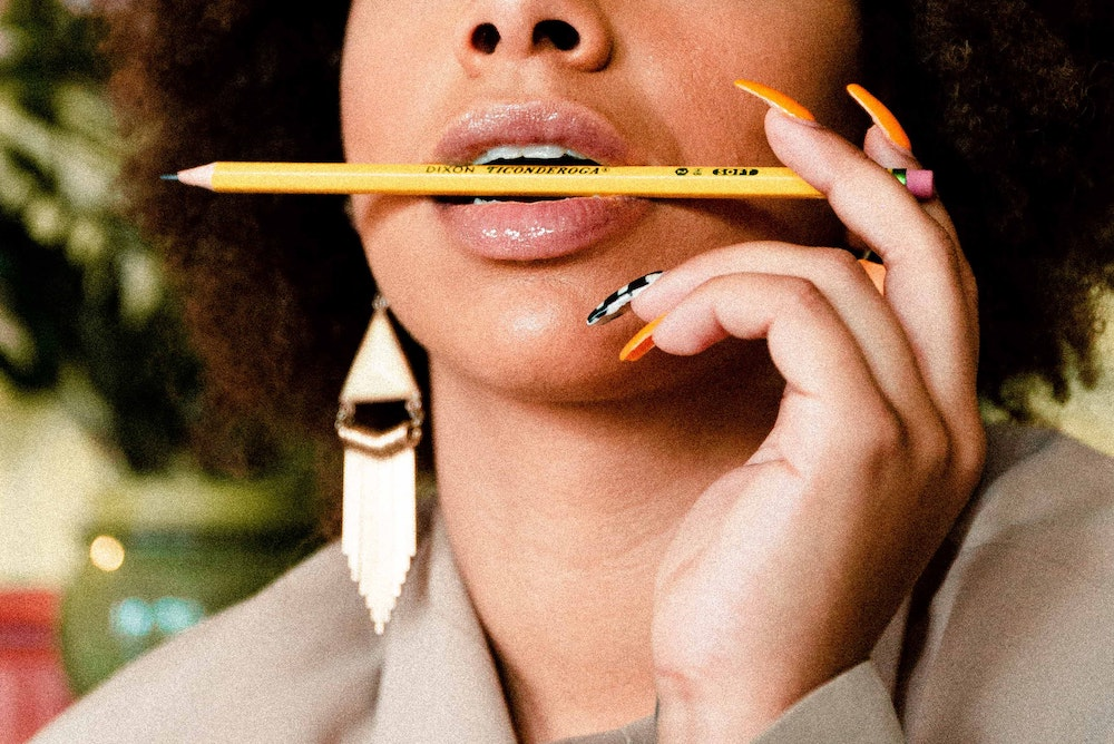 Black woman holding pencil in her mouth