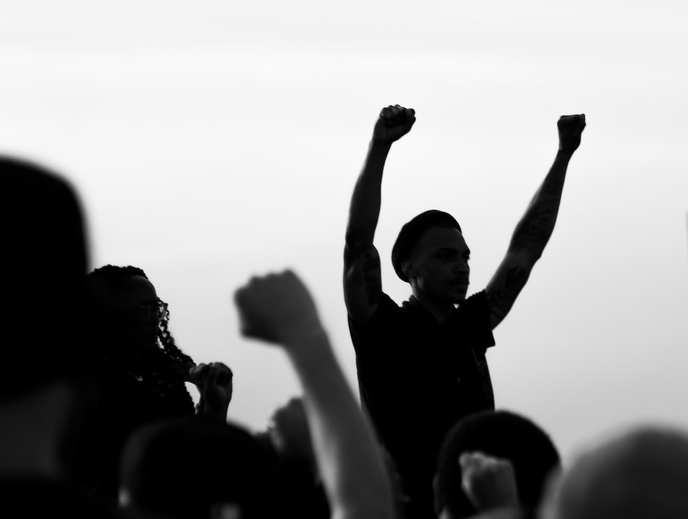 A man in silhouette raises two fists over his head
