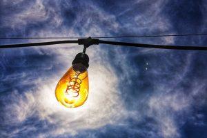 Light bulb against cloudy sky