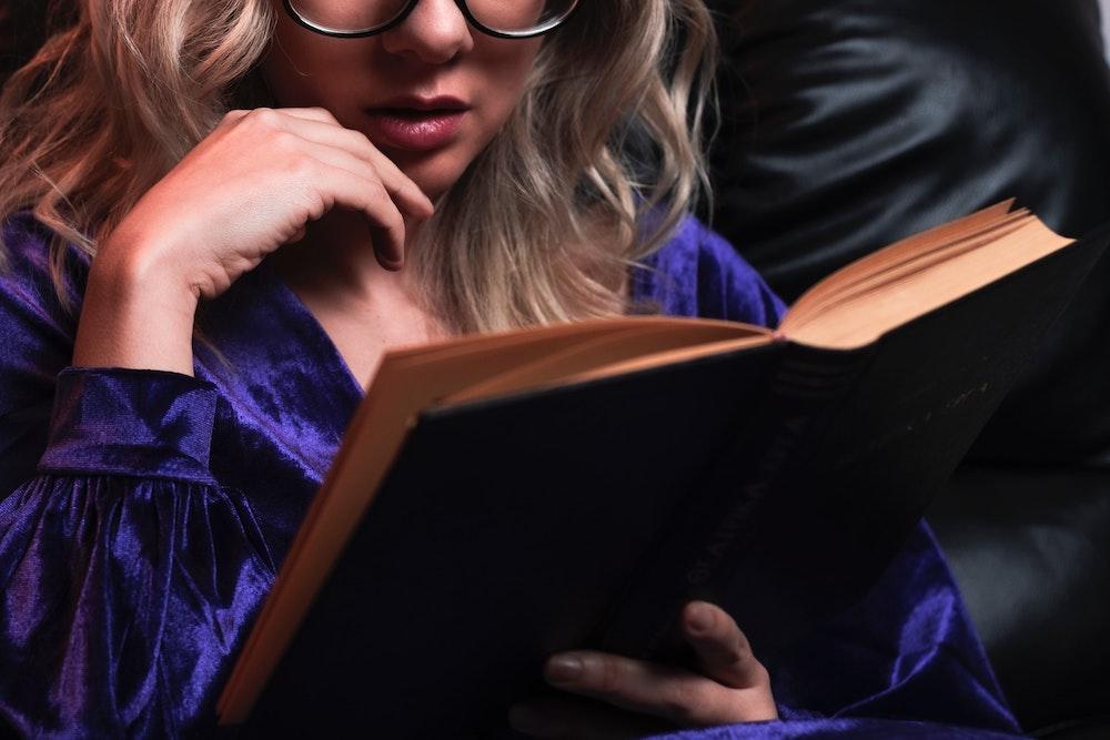 A woman in a purple satin bathrobe reading a book