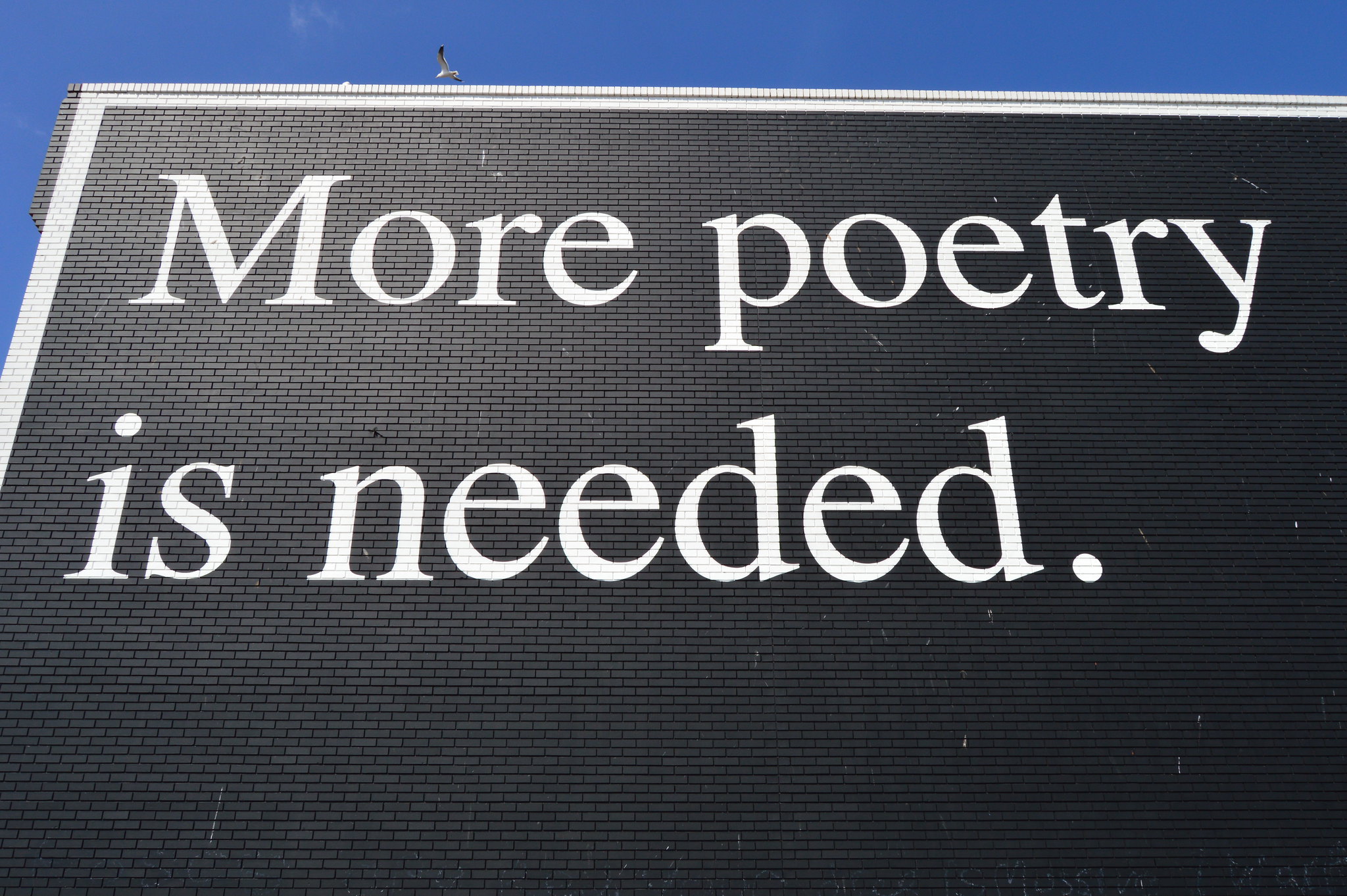 "White text on black wall reading ""more poetry is needed"""