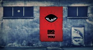 """Grey wall with red square reading """"Big Brother is watching you"""" with an eye icon"""