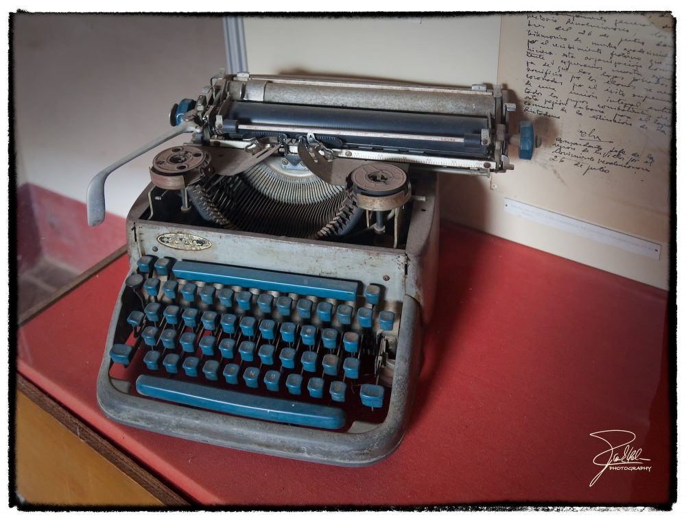 Grey typewriter with blue keys on red desk