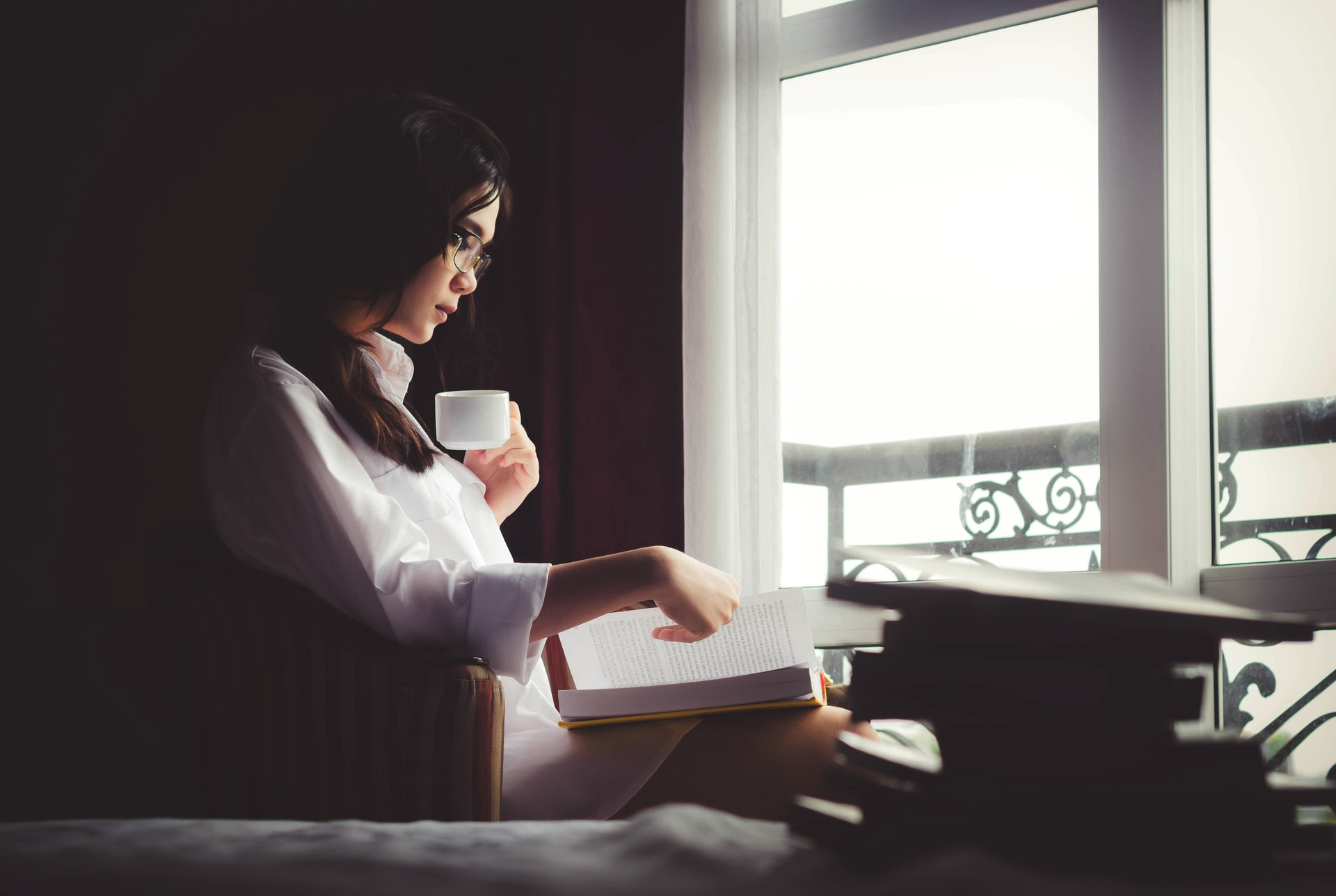 Asian woman reading with a cup of coffee by a window