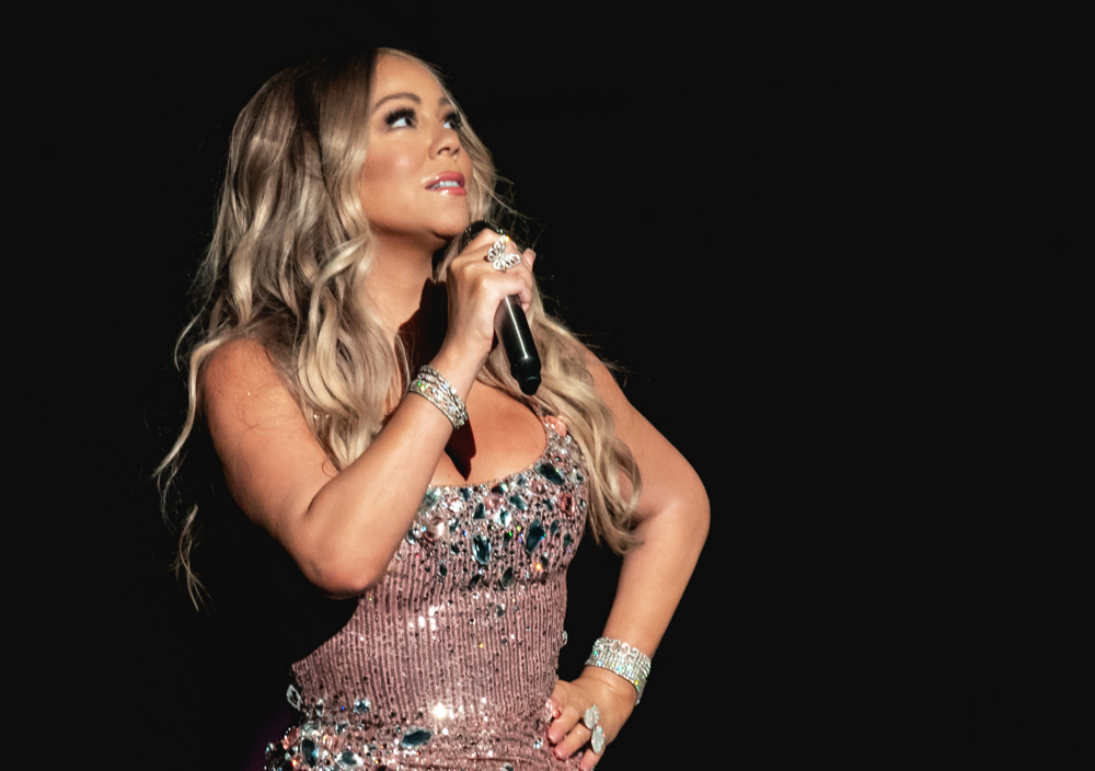 Mariah Carey on stage with a microphone, wearing a sequined gold dress