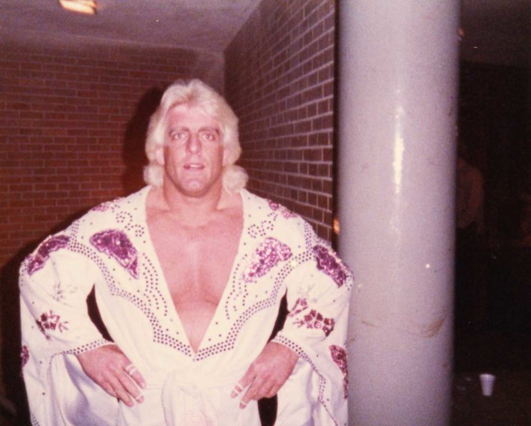 Vintage-looking photograph of Ric Flair in an ornately embroidered white costume with a plunging neck