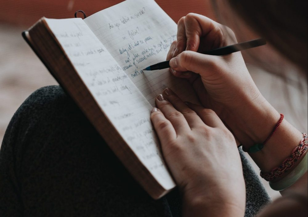 Young woman writing by hand in a diary