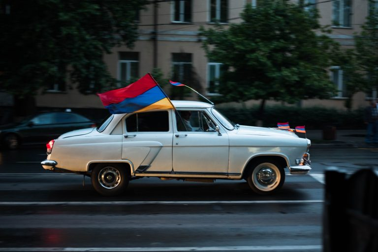 Car flying Armenian flag (red, blue, and gold stripes)