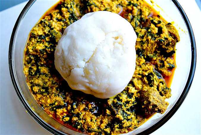 Stew of finely chopped vegetables and meat with a ball of pounded yam on top