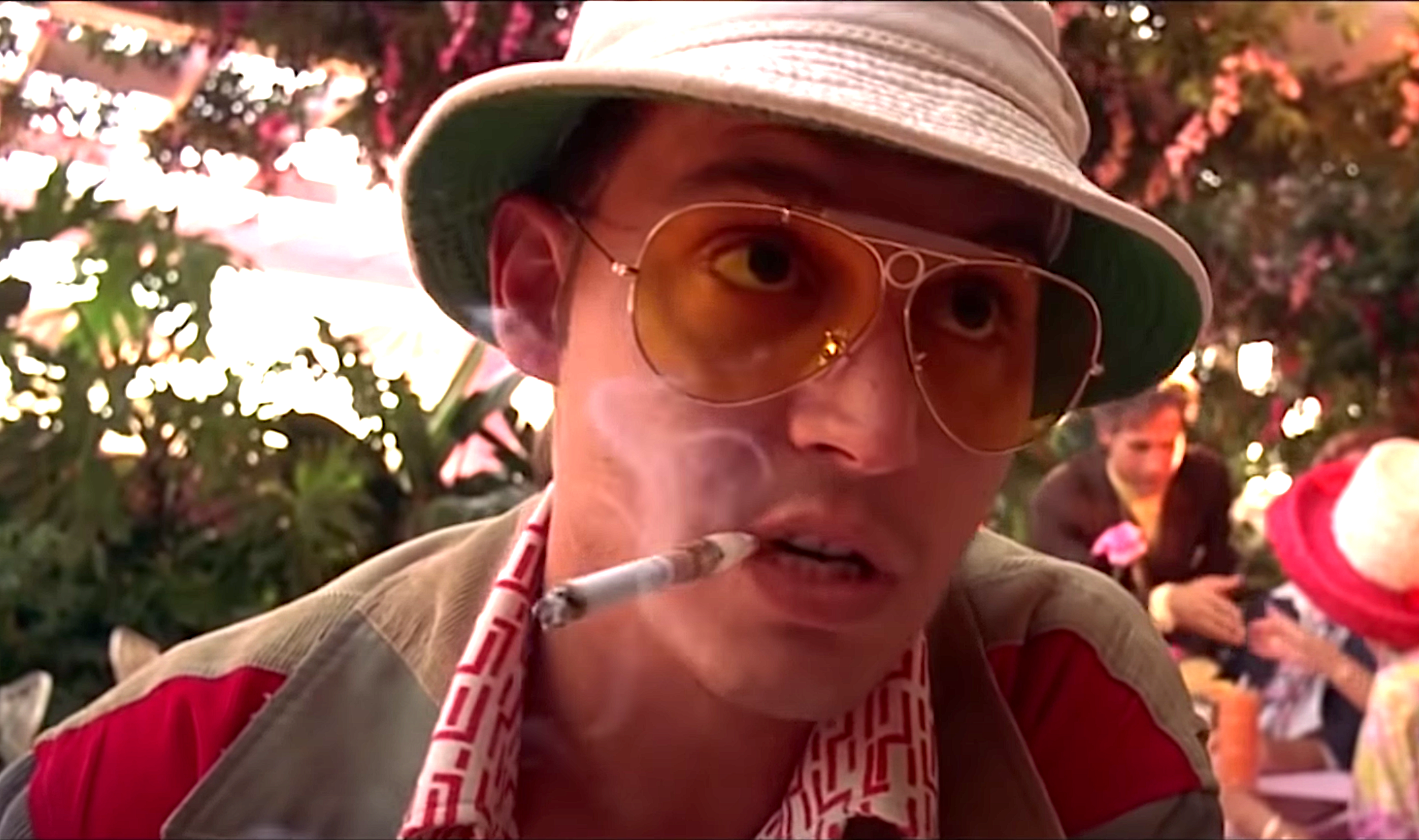 Johnny Depp as Hunter S. Thompson wearing yellow aviator sunglasses and smoking a cigarette