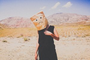 Person wearing a paper bag with a frowny face on it