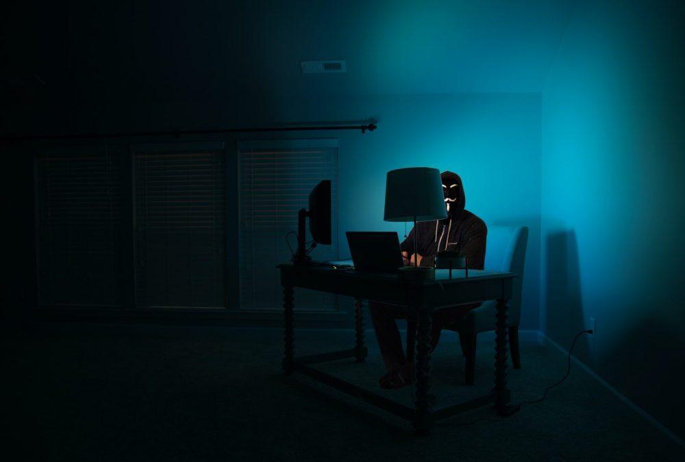 Masked man sitting behind computer
