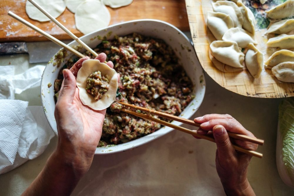 Older woman's hands filling a dumpling using chopsticks