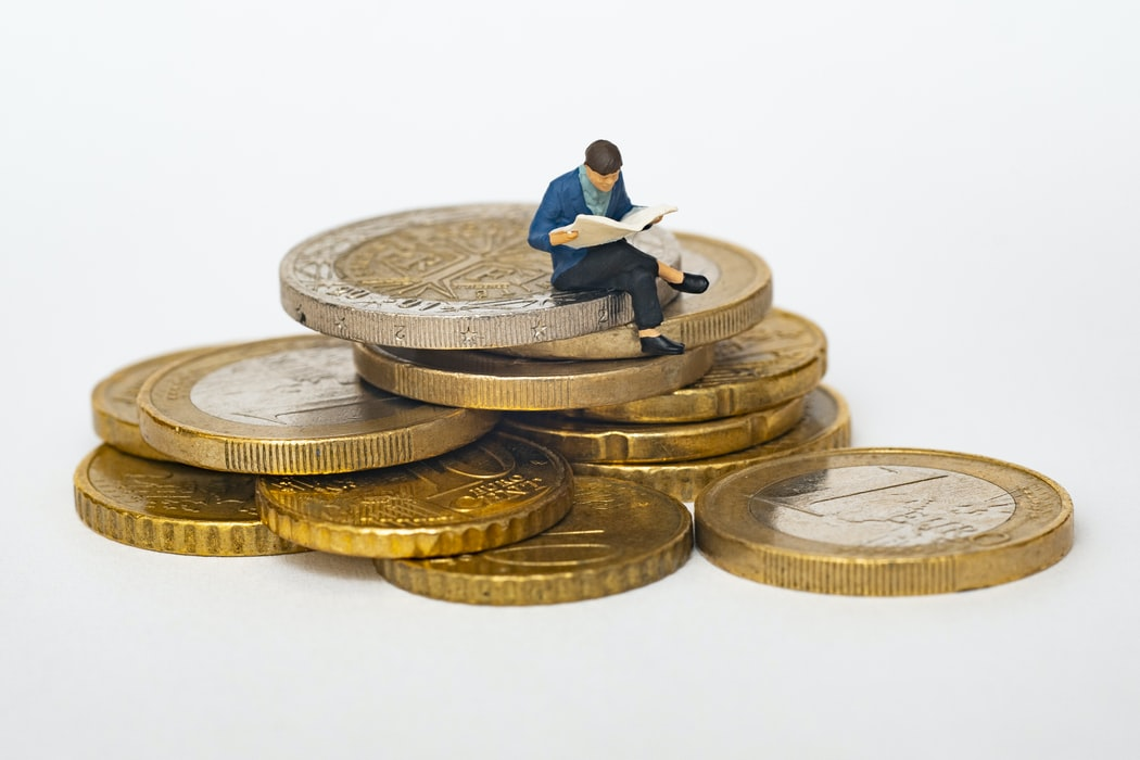 Toy person sitting on pile of coins