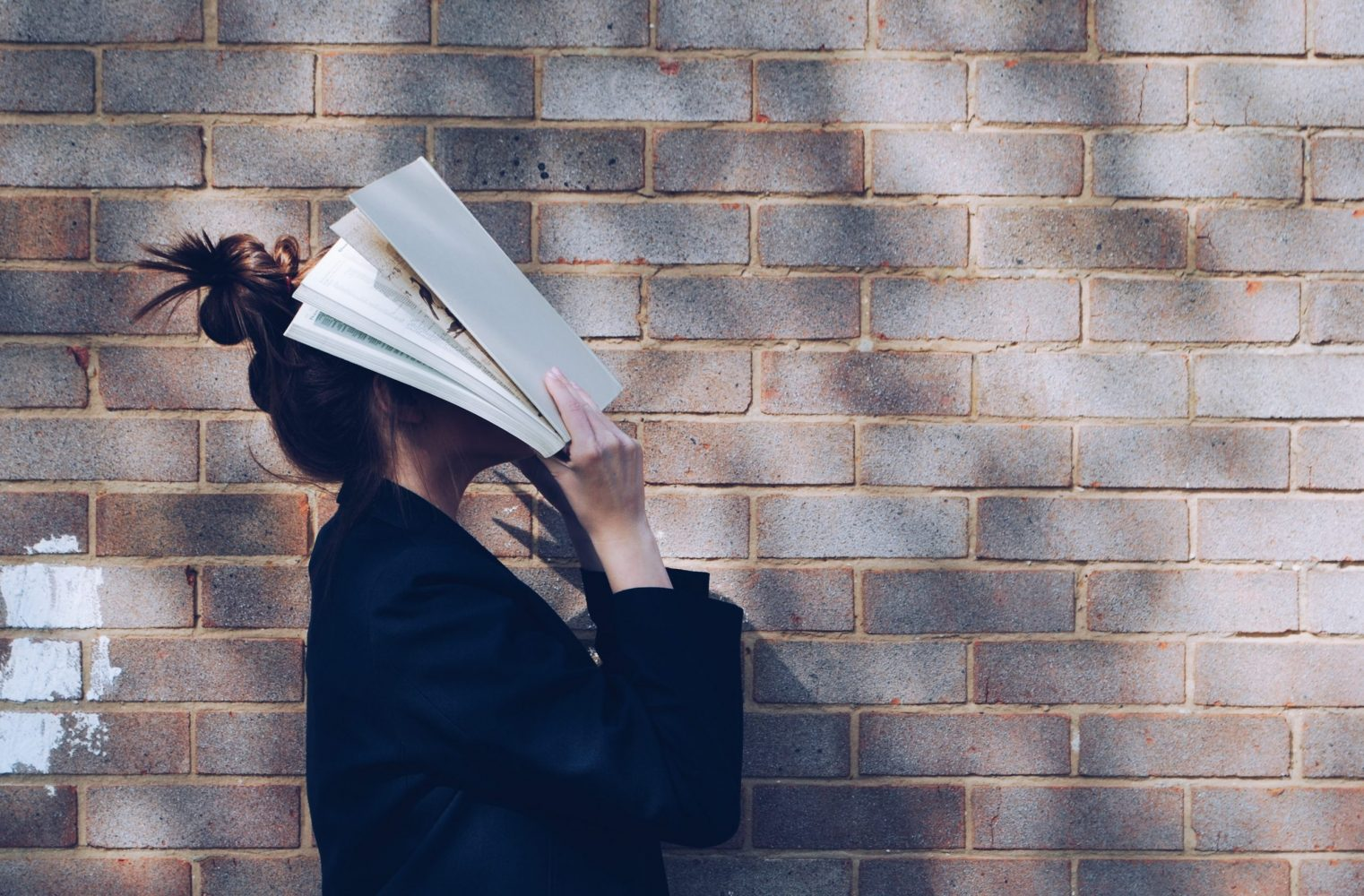 Woman with book over her face