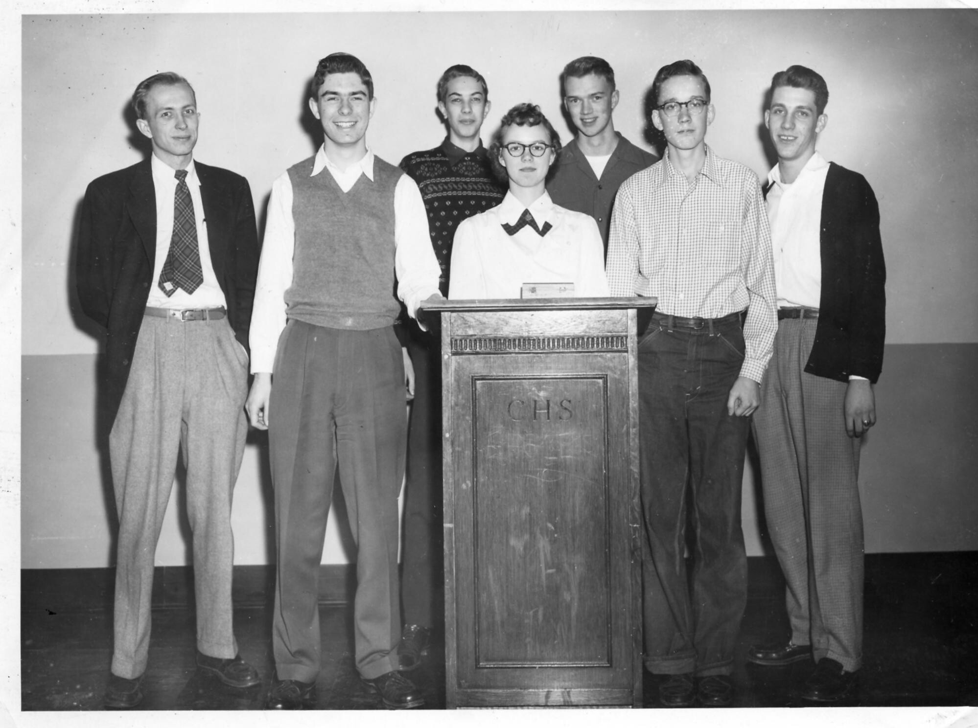 Black and white photo of a mid-century high school debate team. There are six skinny white men with various nerd accoutrements like glasses, sweater vests, and ill-fitting clothes, and one white woman with glasses standing behind a podium.
