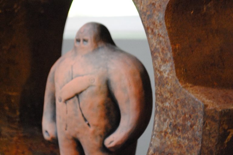 Golem figurine, a terra cotta-colored bulky humanoid figure with very little definition except for two eyes on its nub head