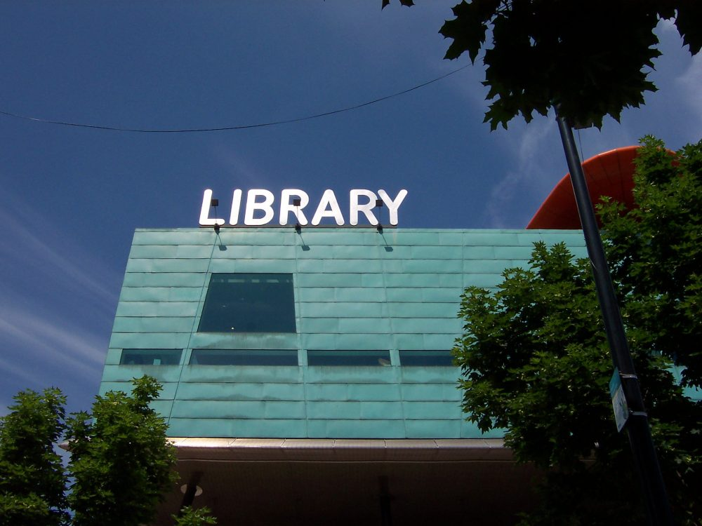 Boxy building with blue-green siding and an illuminated white sign reading LIBRARY on top