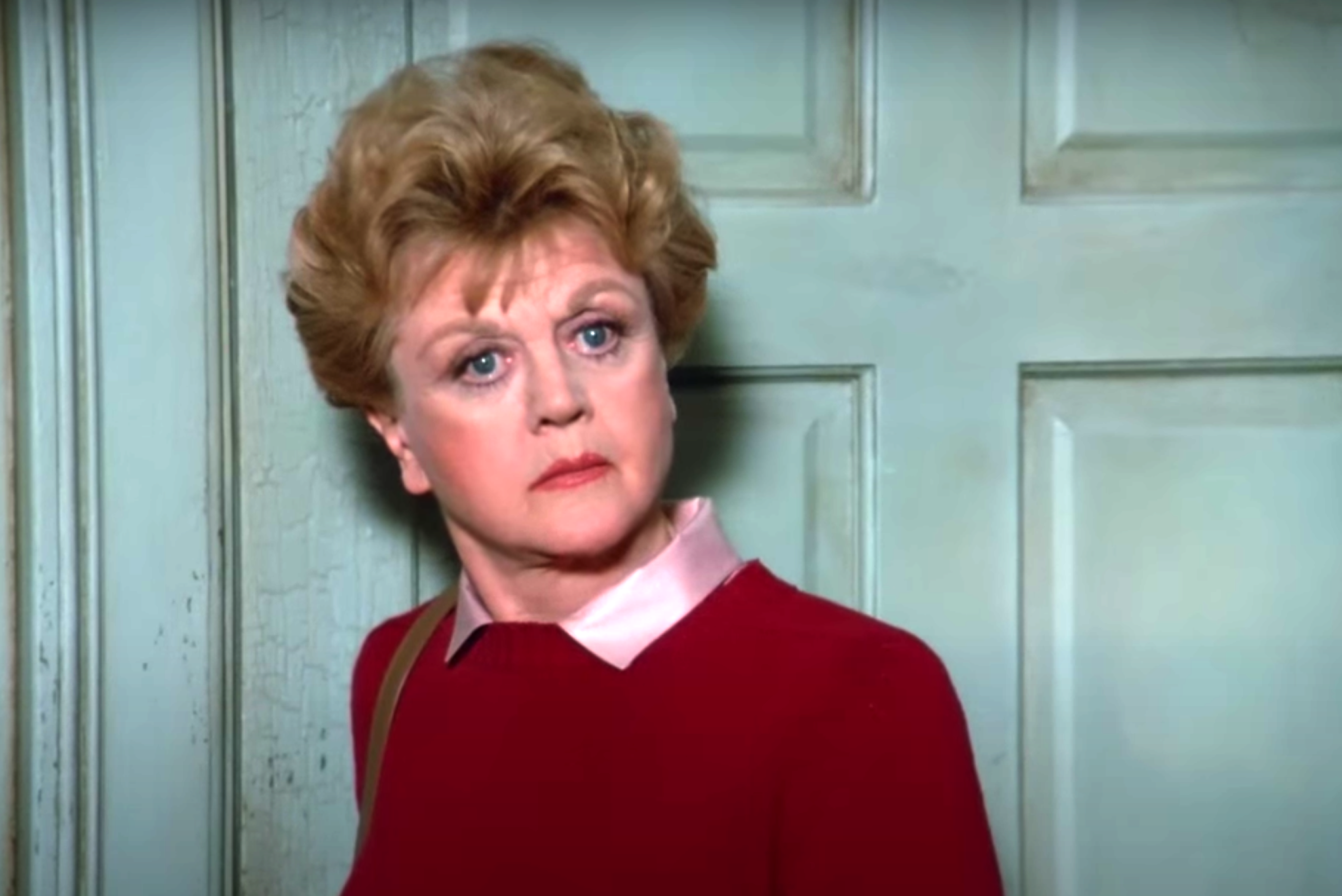 """Screenshot from """"Murder, She Wrote,"""" showing Jessica Fletcher standing in front of a mint green door looking quizzical and wearing a pink collared blouse and maroon sweater"""