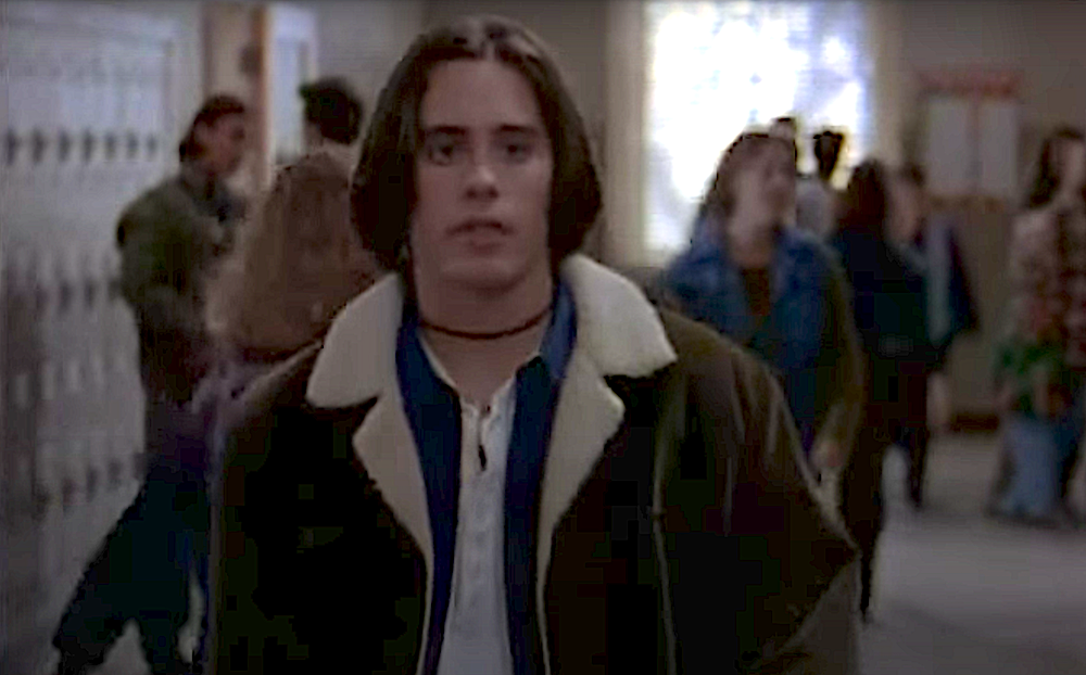 Jared Leto as Jordan Catalano. He is a young white man with chin-length hair wearing a choker necklace, layered shirts, and a jacket with a sheepskin collar