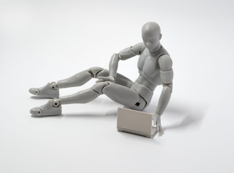 Humanoid silver figure with articulated joints typing on a laptop