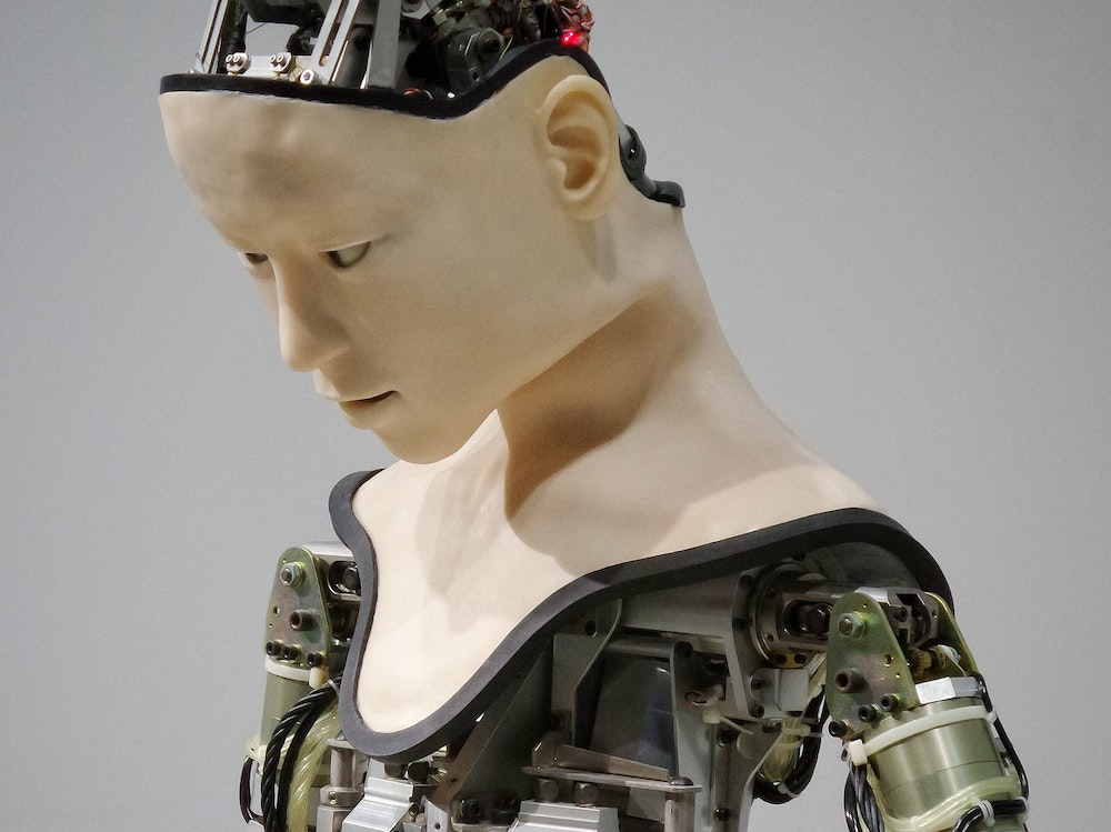 Android with a human-like skin on its face and neck but bare circuit boards on head, shoulders, and chest
