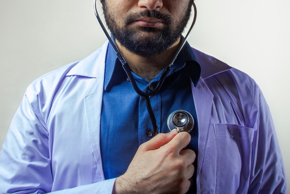 Man with brown skin and beard wearing lab coat and dress shirt, holding a stethoscope to his own chest
