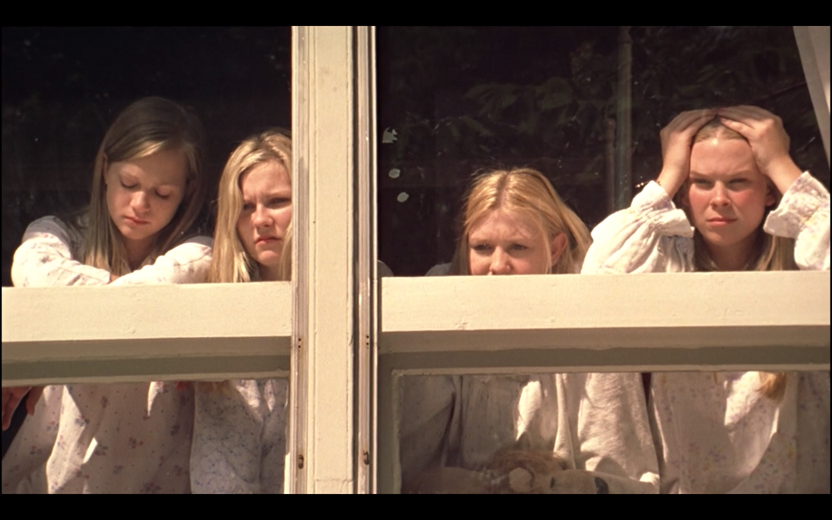 Still from the movie of four girls looking out of a window