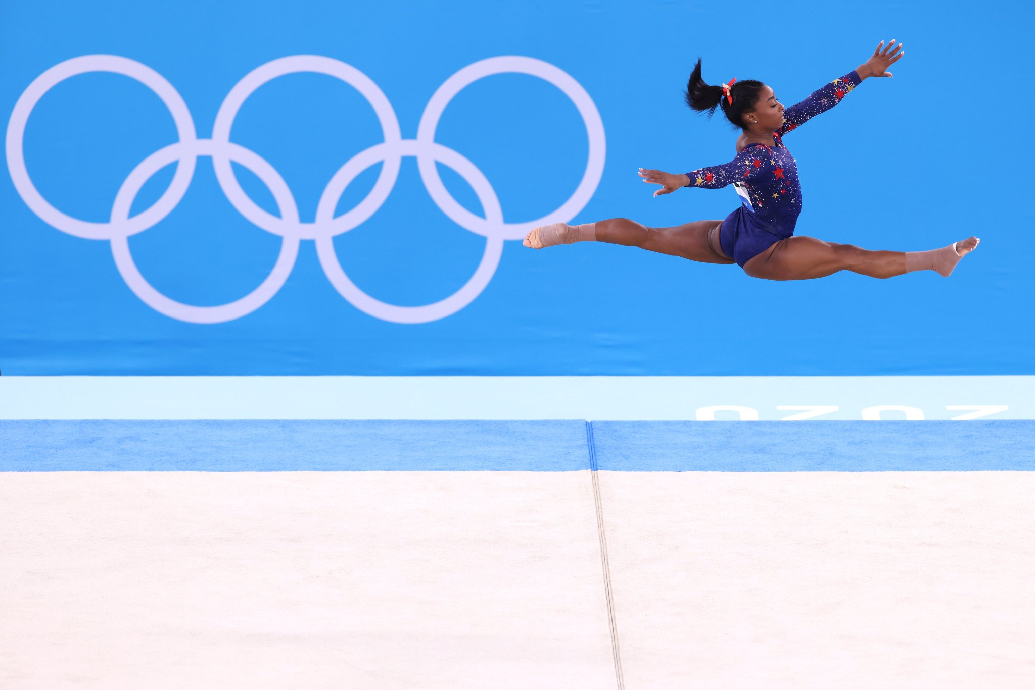Simone Biles mid air in a split during her gymnastics routine at the 2020 Summer Olympics.