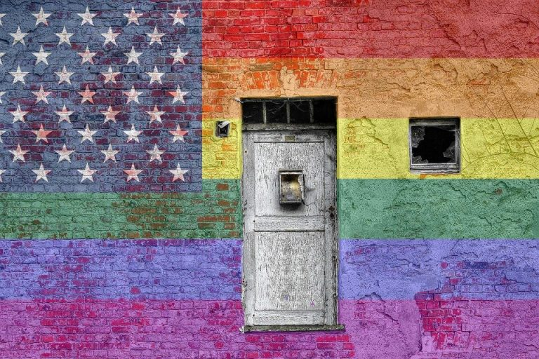 A wall is painted with an American flag with rainbow stripes